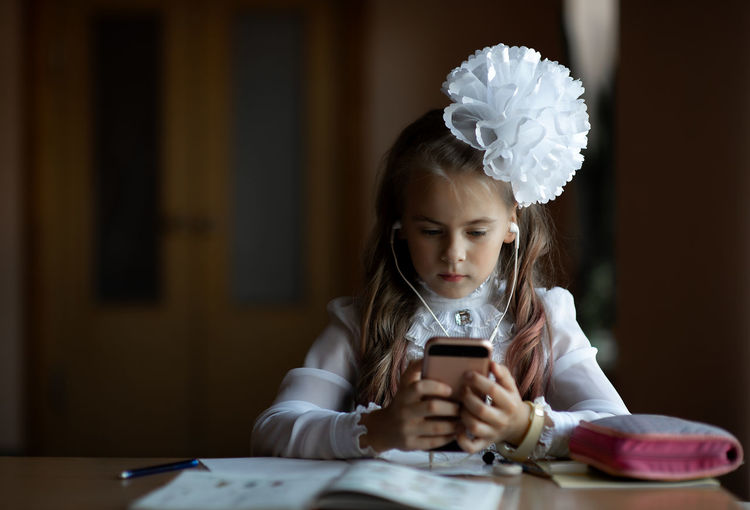 Girl listening to music while using phone at desk in classroom