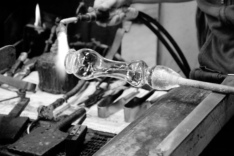 Midsection Of Worker Blowing Glass In Factory