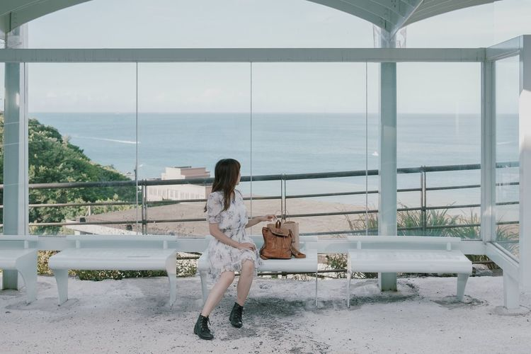 Woman sitting on bench by sea