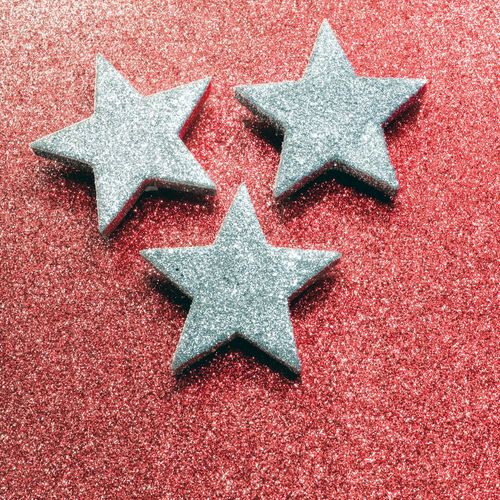Close-Up Of Silver Star Shapes On Red Table