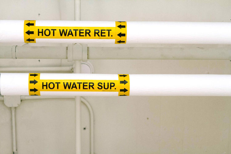 Close-Up Of Text On Water Pipes At Factory