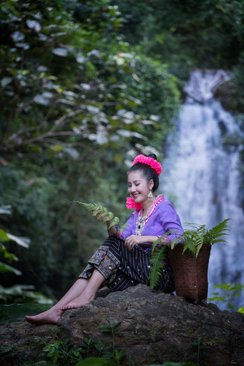 Smiling Young Woman Wearing Traditional Clothing While Sitting Against Waterfall In Forest