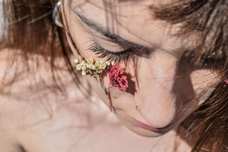 Close-up of woman with flowers on cheek