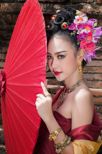 Portrait Of Young Woman In Traditional Clothing Holding Umbrella While Standing Against Brick Wall