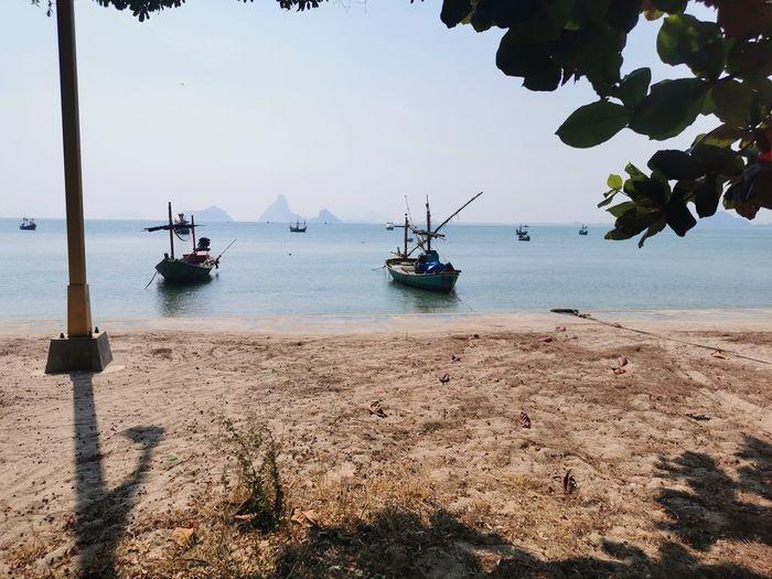 Sailboats on beach against sky