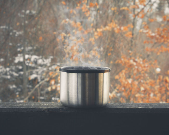 Steam coming from a warm tea Cup Of Tea Smoke Steam Tea Warm Tea Container Cup Day Focus On Foreground Food And Drink Forest Metal Nature No People Outdoors Plant Silver Colored Single Object Still Life Tea Steam Tree Wood - Material EyeEmNewHere