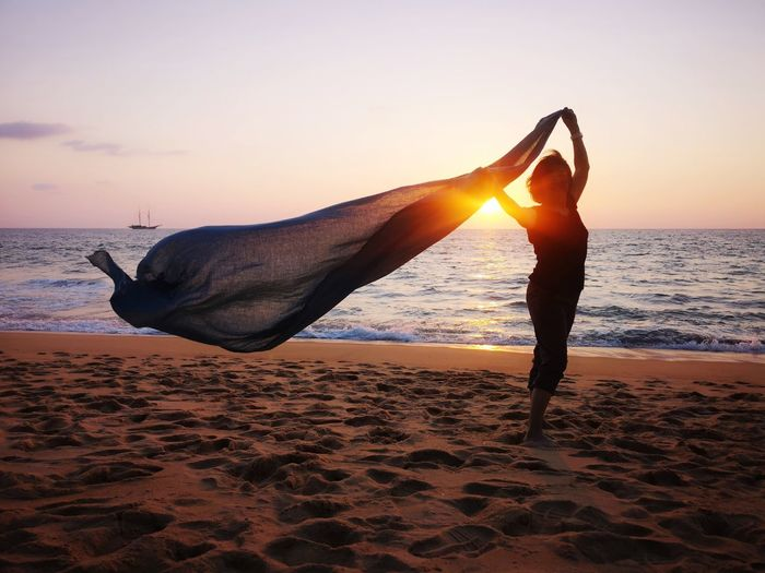 Side view of woman holding fabric while standing at beach against sky during sunset
