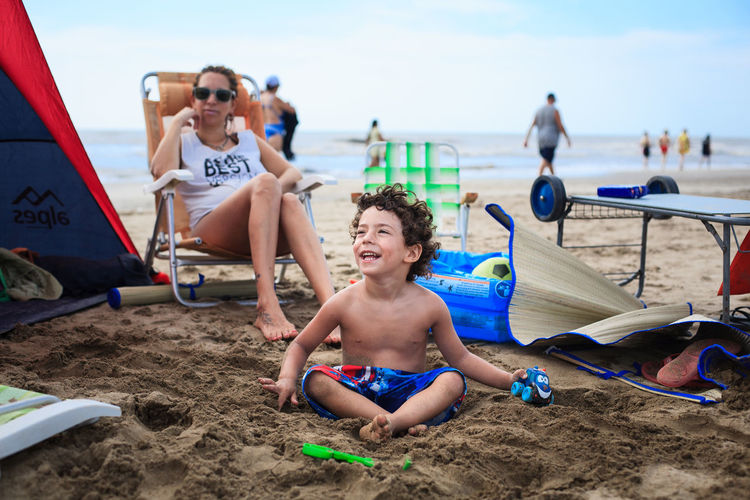 Mother looking at shirtless son sitting with toys on beach