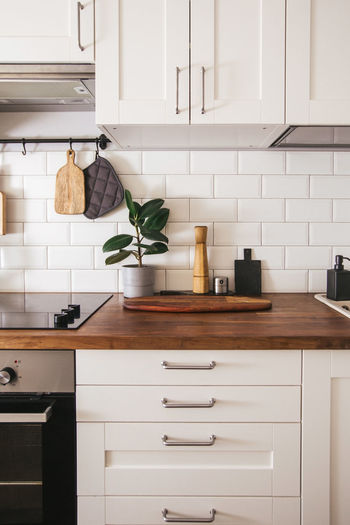 Kitchen brass utensils, chef accessories. hanging kitchen with white wall and wood tabletop.
