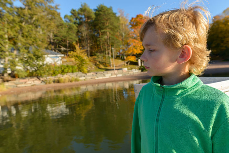 Portrait of boy looking at lake