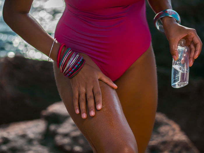 Afro Black Woman Body & Fitness Oil Body Abdomen Adult Beach Close-up Day Focus On Foreground Human Body Part Human Hand Legs Leisure Activity Lifestyles Low Section Midsection One Person Outdoors People Real People Touching Water Women Young Adult