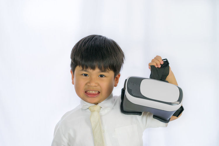 Portrait of boy holding virtual reality simulator against white background