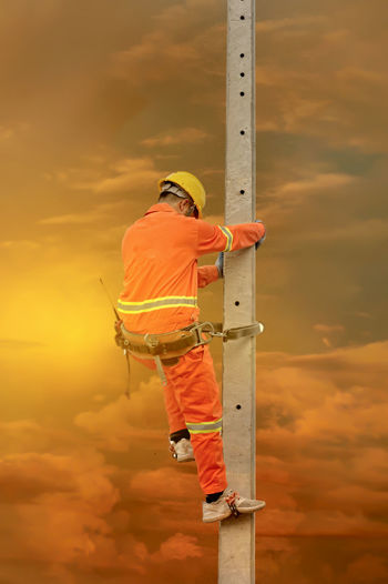 Man working on ladder against orange sky