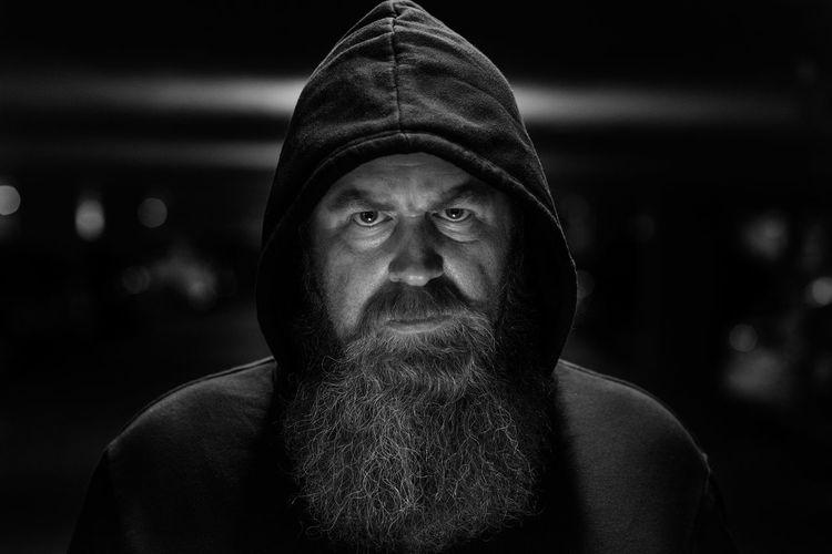 Portrait of serious bearded mature man wearing hoodie in darkroom