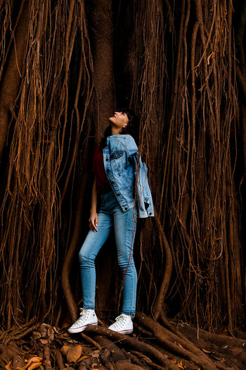 Full length of young woman posing while standing against tree trunk