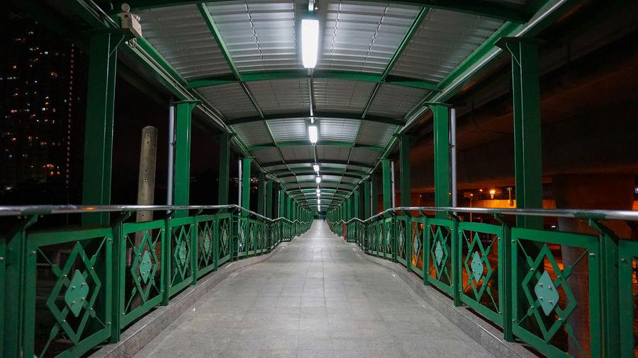 Empty footbridge in illuminated tunnel