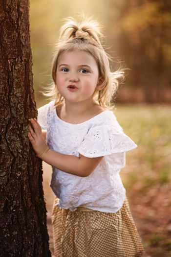 Portrait of cute girl standing on tree trunk
