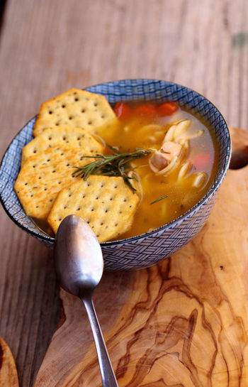 Chicken noodle soup in a blue and white bowl with crackers, all sitting on a wood cutting board. Bowl Broth Chicken Noodle Soup Chicken Soup Comfort Food Crackers Cutting Board Food Healthy Home Remedies No People Sick Soup Spoon Wood Wooden Spoon