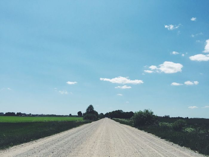 Dirt Road Amidst Fields Against Sky