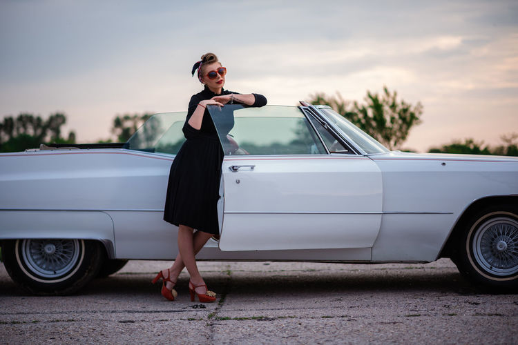 Full length of woman standing on car