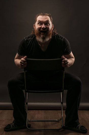 Adult Beard Black Background Chair Facial Hair Front View Full Length Indoors  Looking At Camera Males  Mature Adult Mature Men Men Mid Adult Mid Adult Men One Person Portrait Real People Seat Sitting