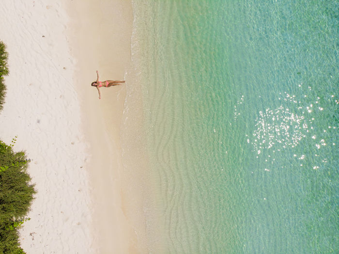 Droneshot of a girl in bikini on paradise beach Drone  Droneshot Aerial View Island Tropical Maldives Blue Water Beach Waves Crashing From Above  Palm Tree Palm Trees Paradise Blue Green Bikini No People Waves, Ocean, Nature Islands Unspoiled Nature Nature Landscape Landscapes Paradise Beach Perfection
