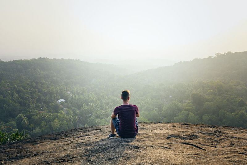 Rear view of man sitting on mountain against sky