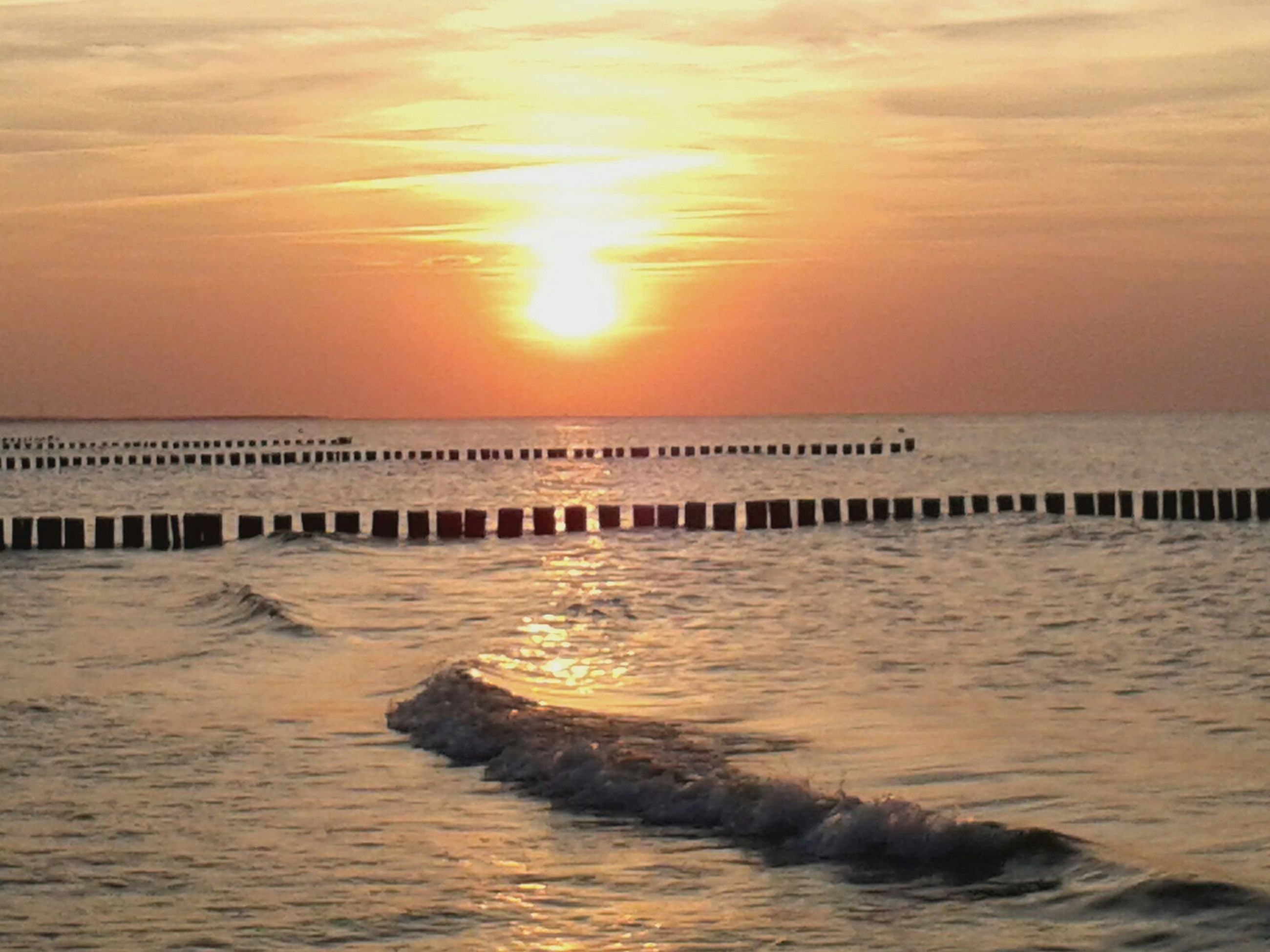 sunset, sea, water, horizon over water, scenics, tranquil scene, sky, beauty in nature, orange color, tranquility, waterfront, pier, idyllic, nature, wooden post, rippled, reflection, built structure, silhouette, sun