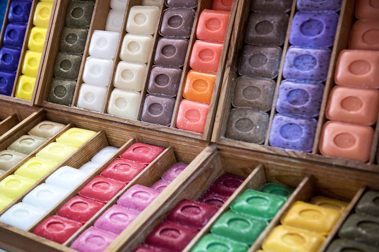 Rows of colorful French Marseille hard soaps arranged in boxes Hygiene Marseilles Natural AssoRted Colorful Display French Handmade In A Row Multi Colored Rack Scented Shop Soap Traditional Variation
