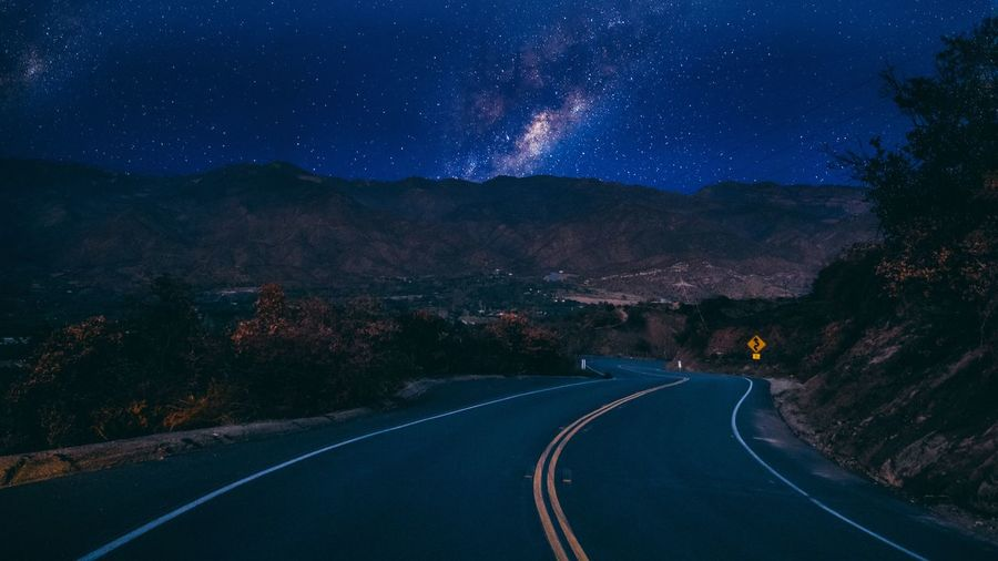 Road amidst mountains against sky at night