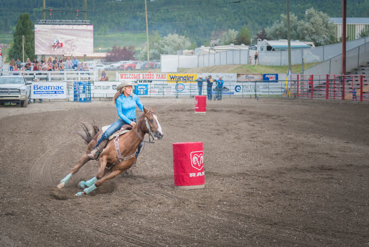 Williams Lake, British Columbia/Canada - June 30, 2016: a barrel racer swerves around the second barrel at the 90th Williams Lake Stampede, one of the largest stampedes in North America 90th Williams Lake Stampede Arena British Columbia, Canada Canadian Professional Rodeo Association Event Travel Woman Barrel Racing Candid Competition Country Western Cowgirl Dangerous Documentary Editorial  Extreme Sports Fast Horse Professional Rodeo Race Rodent Speed Stampede Tourism Western Dress