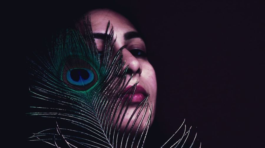 Portrait of young woman with peacock feather against black background