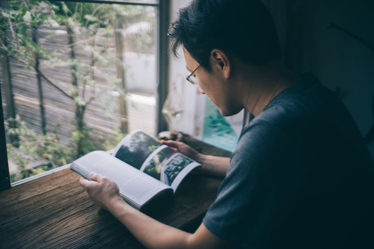 Asian  Reading Relaxing Activity Asian Boy Asian Man By The Window Casual Clothing Holding Indoors  Leisure Activity Lifestyles Looking One Person Real People Sitting Young Adult