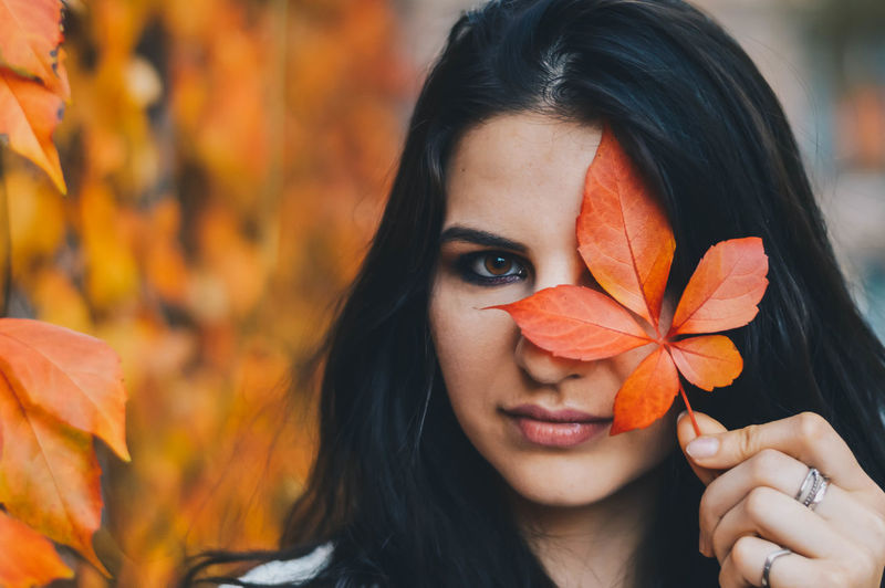 Close-up portrait of young woman with orange leaves during autumn
