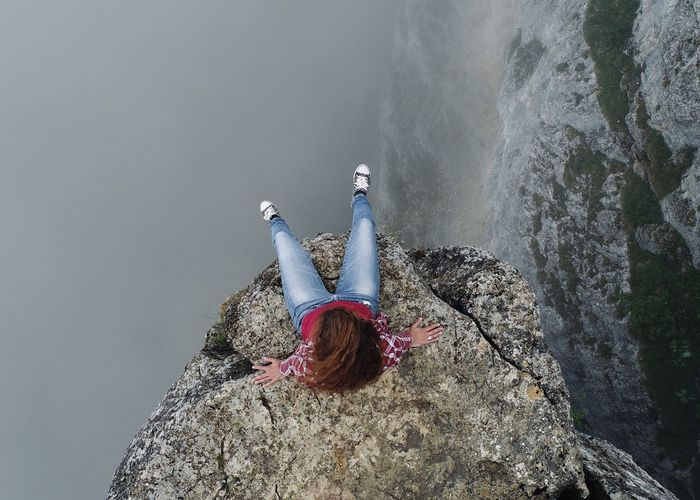 Directly above shot of woman sitting on cliff by lake