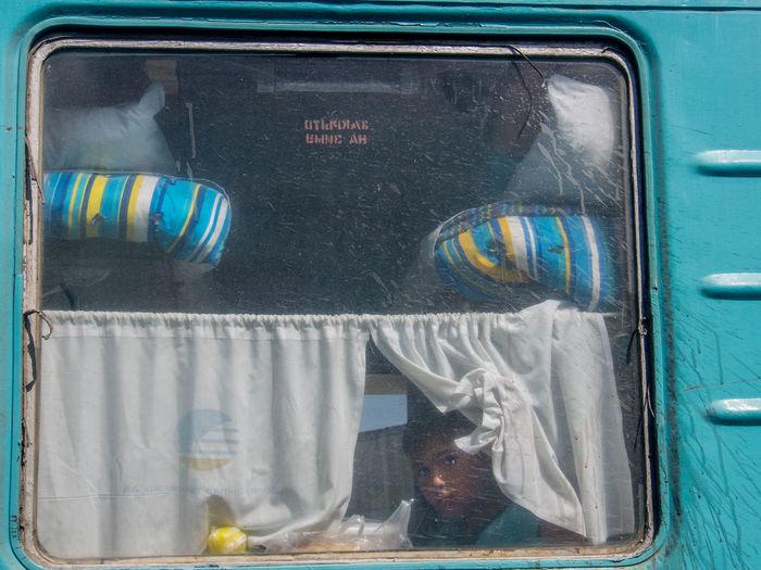 Child looking from a window of the overnight train Almaty-Aralsk, Kazakhstan Kazakhstan Close-up Curtain Peeking Sleeper Train Transportation Window