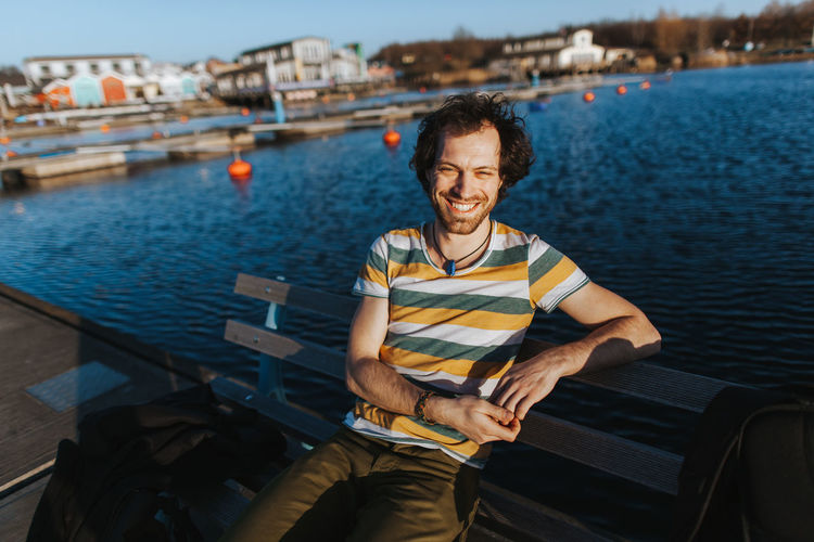 Portrait Of Smiling Man Sitting On Bench Against Sea