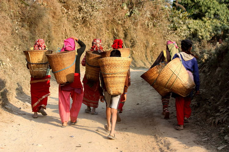 Rear view of people carrying baskets on dirt road