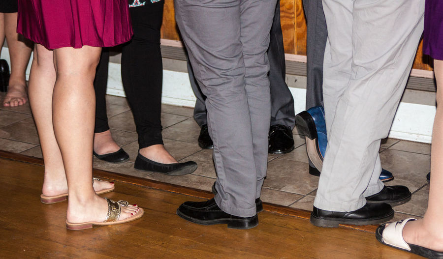 Low section of people standing on hardwood floor during party