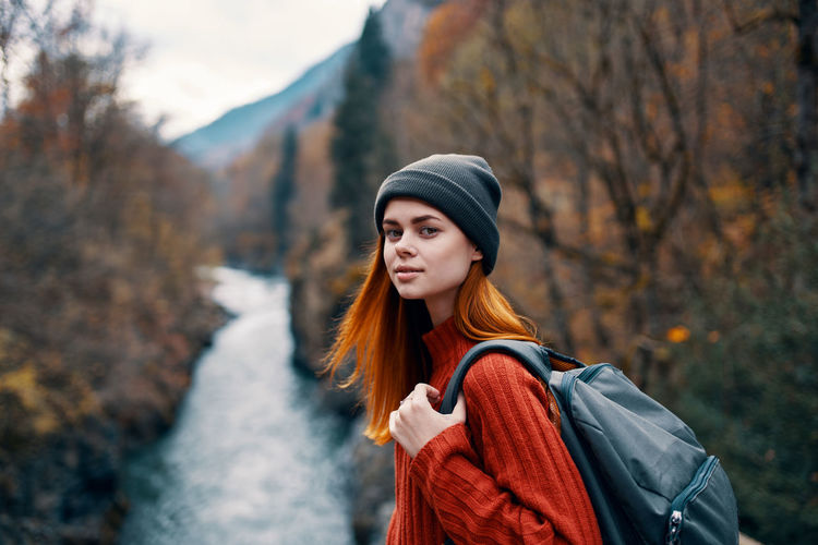 Portrait of beautiful young woman standing against trees during winter