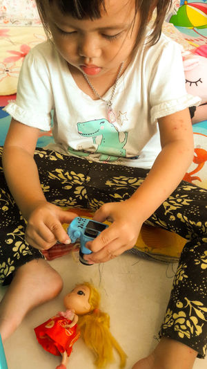 High angle view of cute girl playing with toys at home