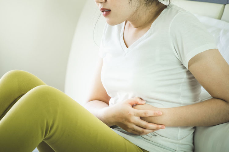 Midsection of woman with stomachache sitting on bed at home