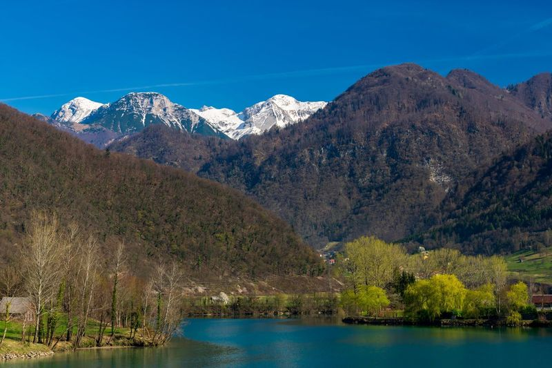 Lake called Bridge on Soča in Slovenia and snowy peaks in the background. Tree Water Mountain Snow Lake Snowcapped Mountain Mountain Peak Sky Mountain Range