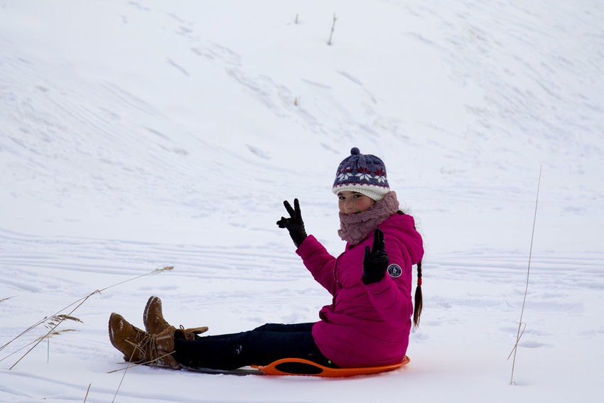 Happy teenage girl moved off the snow slide on a sleigh Happy Outdoor Activity Sled Sleigh Activity Cold Temperature Day Knit Hat Leisure Leisure Activity Lifestyles Nature One Person Outdoors Real People Ski Holiday Sledding Smiling Snow Teenage Girls Vacations Warm Clothing Weather Winter Winter Fun
