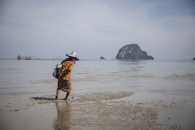 Woman Collecting Oysters On Beach