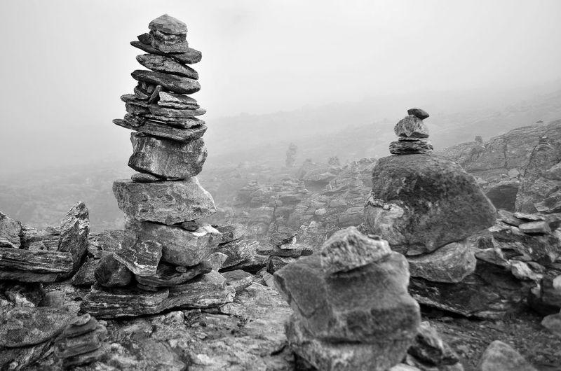 Stack of cairns on landscape against sky