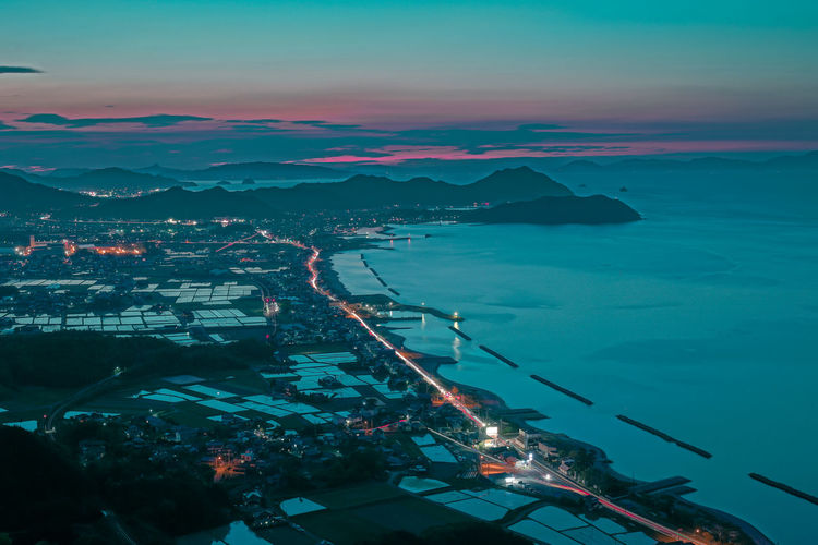 Aerial view of illuminated cityscape by sea against sky at night