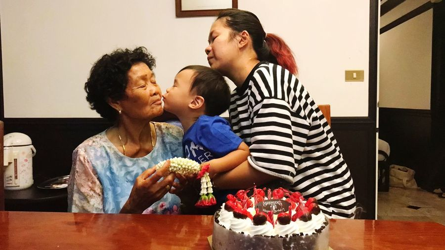 Grandson kissing grandmother by birthday cake on table at home