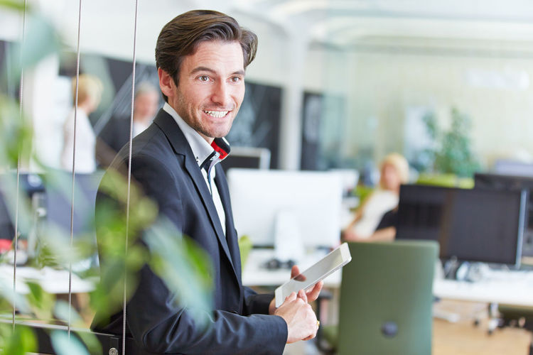 Side view of businessman using digital tablet while standing in office