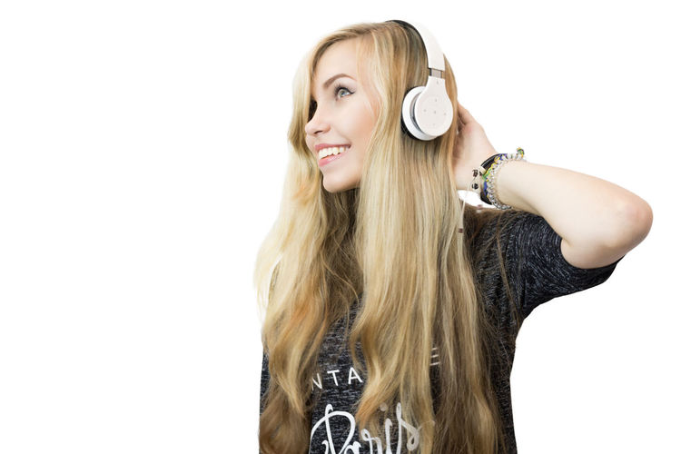 Smiling Young Woman Listening Music Against White Background